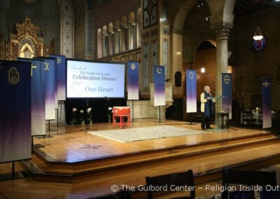 Banners on the stage represent the religious communities represented by Advisors to The Guibord Center, attending the One Heart Celebration Dinner